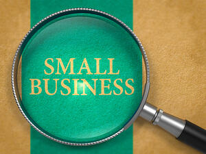 Small Business Concept through Magnifier on Old Paper with Blue Vertical Line Background.