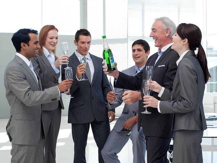 Smiling business people celebrating a success with Champagne.jpeg